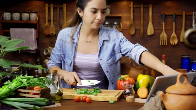 digital tablet recipe: dolly shot of hispanic young woman chopping vegetables for preparing food - woman cooking stock videos & royalty-free footage