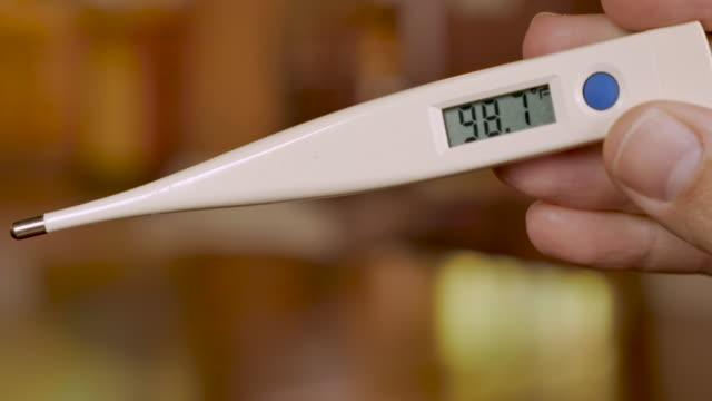 vidéos et rushes de thermomètre numérique affichant 98.7 degrés fahrenheit - température normale - température
