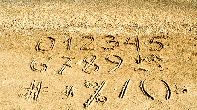 Digits & signs written on a beach sand.