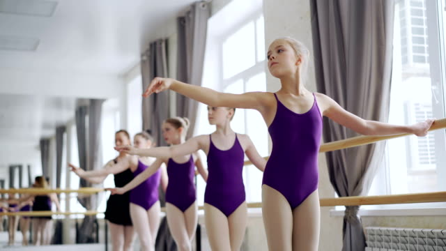 diligent ballet students are practising arm movements during class in studio. teacher professional ballerina is helping them correcting positions and giving instructions. - body abbigliamento sportivo video stock e b–roll