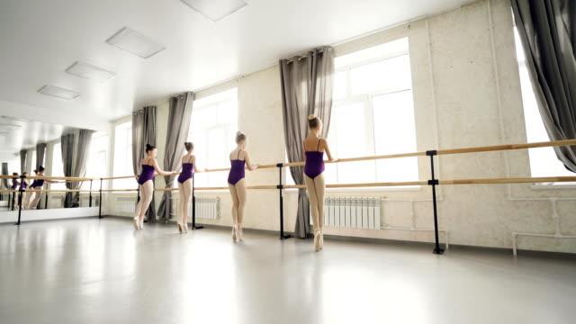 flitiga barn balettdansare gör övningar dans på tiptoes hålla balett barre medan deras lärare kontrollera fötter position och att hjälpa eleverna. - dansbana bildbanksvideor och videomaterial från bakom kulisserna