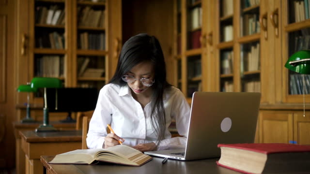 diligent female student biologist writing at table with book and laptop in library - lawyer stock videos and b-roll footage
