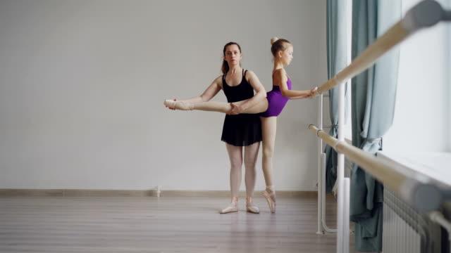 ボディー スーツで勤勉なほとんどのバレエ学生を持つプロ教師の動きおよび足の後方を上げる位置を学び個々 のバレエ レッスンです。 ビデオ