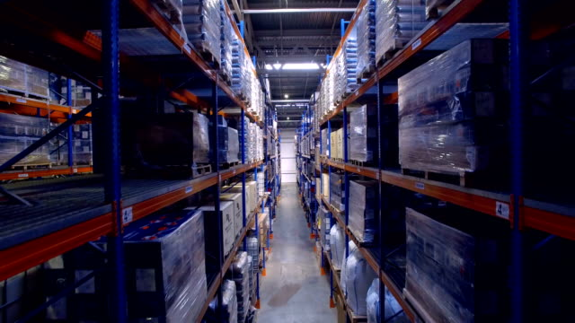 A dimly lit warehouse with assortment of goods on the racks. video