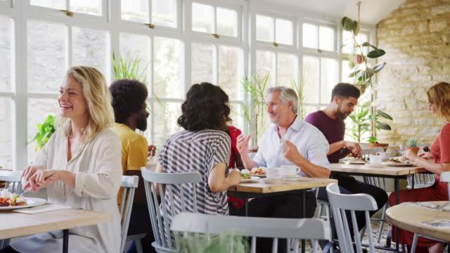 american diner, sprechen und essen während des tages, handheld an tischen in einem gut besuchten restaurant - brunch stock-videos und b-roll-filmmaterial