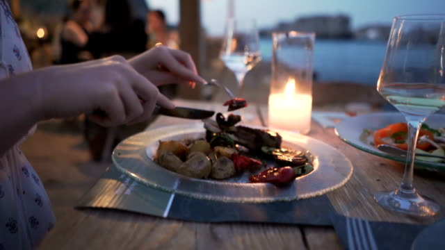 Dining With A View Close-up shot of a young caucasian woman having a dinner at the beach restaurant. indulgence stock videos & royalty-free footage