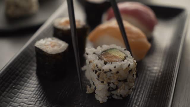 vídeos y material grabado en eventos de stock de cena en un restaurante japonés. comer sushi. - sushi