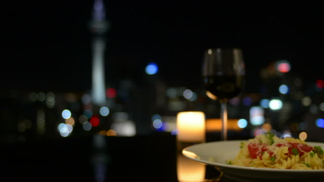 Dinner in front of Auckland city skyline at night video
