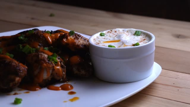 dipping a buffalo chicken wing into bleu cheese or ranch dressing - immergere video stock e b–roll