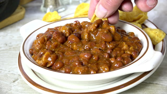 dipping a corn chip in to a bowl of chili - chilli con carne video stock e b–roll
