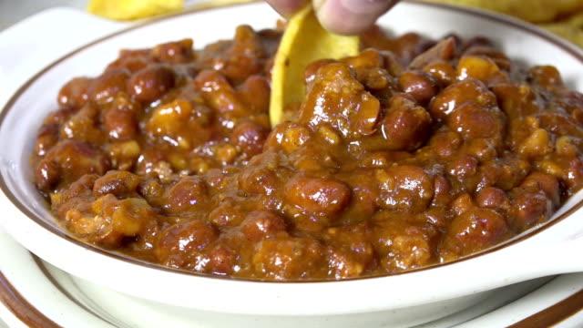 ein maischip in heiße chili tauchen - chilli stock-videos und b-roll-filmmaterial