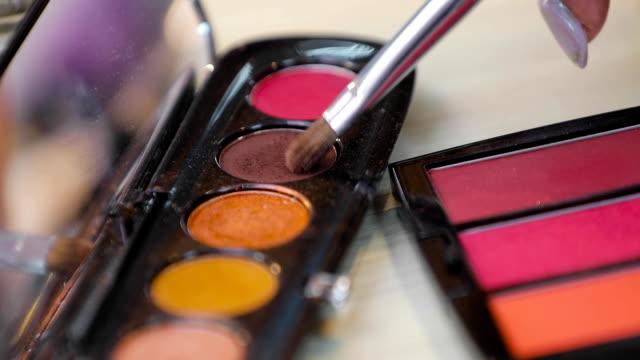 アイシャドウ、化粧のクローズ アップのための装飾品に浸るブラシ - アイシャドウ点の映像素材/bロール