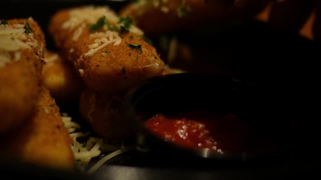 Dipping cheese sticks in tomato sauce - unhealthy appetizer concept - vídeo