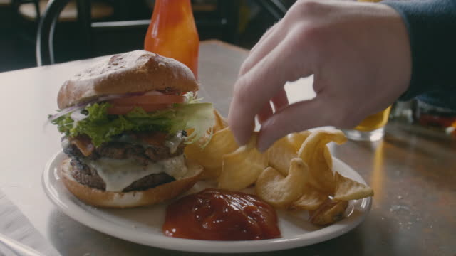 Dipping Curly French Fry in Ketchup Bacon Lettuce Tomato Swiss Cheese Double Burger Eating Food Restaurant Closeup video