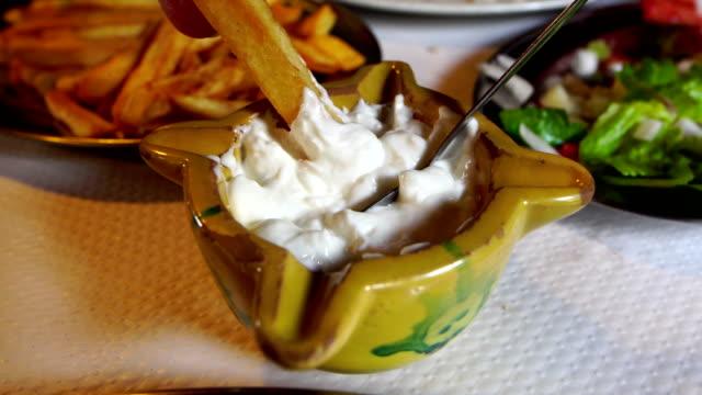 vídeos y material grabado en eventos de stock de sumergir patatas fritas en alioli - plato típico - comida española