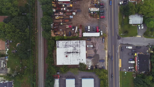 Directly above, looking-down top view of the industrial zone with self-storage hangars in Long Island, New York State, USA. Accelerated aerial drone video with the panning camera motion. Self Storage in the industrial zone in Long Island, New York State, USA. 4K UHD aerial drone video footage. warehouse aerial stock videos & royalty-free footage