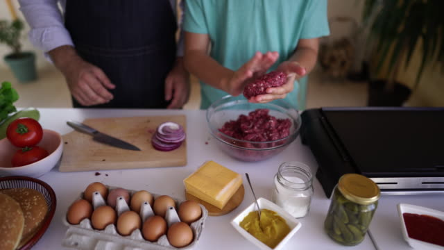 Directly above making burgers of minced meat Unrecognizable boy and men making burgers of minced meat at home, directly above ground beef stock videos & royalty-free footage