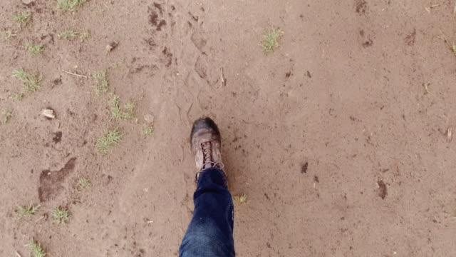 directly above shot of a person wearing jeans and hiking boots walking through mud and puddles of water outdoors - fare un passo video stock e b–roll