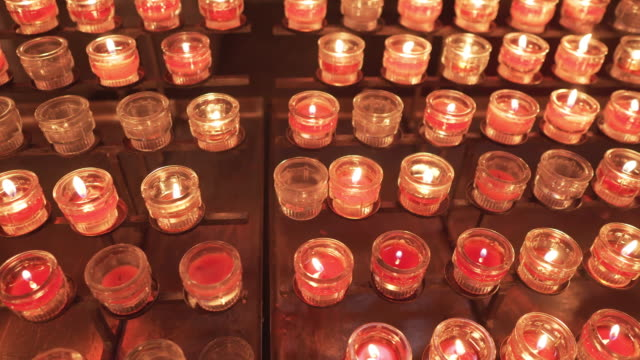 directly above view: Mary and the candles, Red prayer candles burning in a row inside a Catholic church for praying and spirituality, Salzburg Cathedral, the Baroque cathedral of the Roman Catholic Archdiocese of Salzburg city, Salzburg, Austria.
