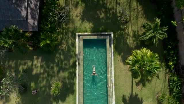vídeos y material grabado en eventos de stock de directamente sobre la vista de la mujer relajante en la piscina - backyard pool