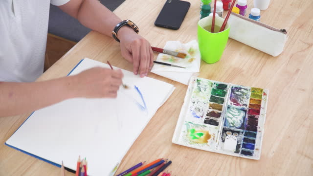 directly above view watercolor paint and equipment such as paintbrush and part Asian handsome man painting one paper page with watercolor to create artist skill and imagination. Concept of young adult and leisure activity at the weekend.
