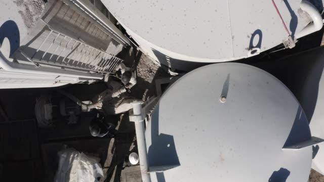 stockvideo's en b-roll-footage met direct boven het hoofd aerial drone shot van twee oilfield workers klimmen down a metal ladder te controleren op modder tanks op een olie-en gasboorpad site op een zonnige dag - gas