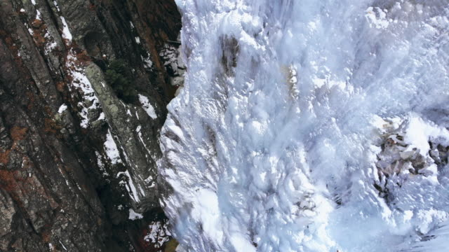 directly overhead aerial drone shot of a narrow mountain canyon with snow, a stream, and a wall of icicles (ice park) in ouray, colorado - ледолазание стоковые видео и кадры b-roll