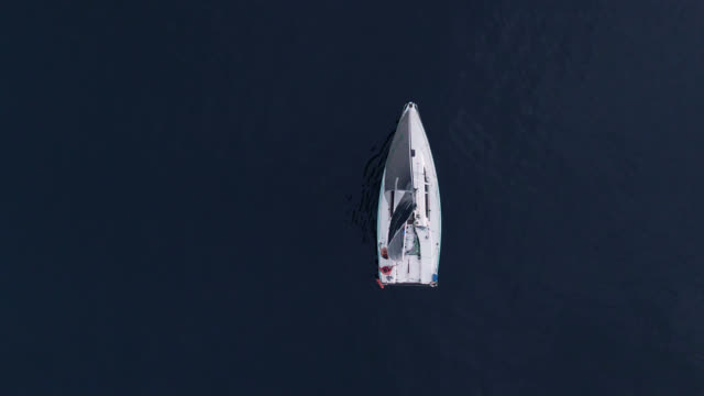 Directly Overhead, Aerial Drone Shot of a Sailboat with a Small Crew Heading Out into the Puget Sound in Washington on an Overcast Day