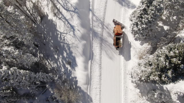 Directly Overhead Aerial Drone Shot of an Orange Tractor Plowing Deep Snow in a Forest in the Mountains in Winter under a Bright, Sunny Sky