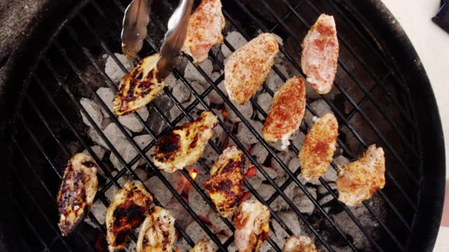 Directly Overhead Shot of a Pair of Metal Tongs Flipping Over Chicken Wings Cooking on an Outdoor Barbecue on a Metal Grate with Lit Charcoal Briquettes Underneath