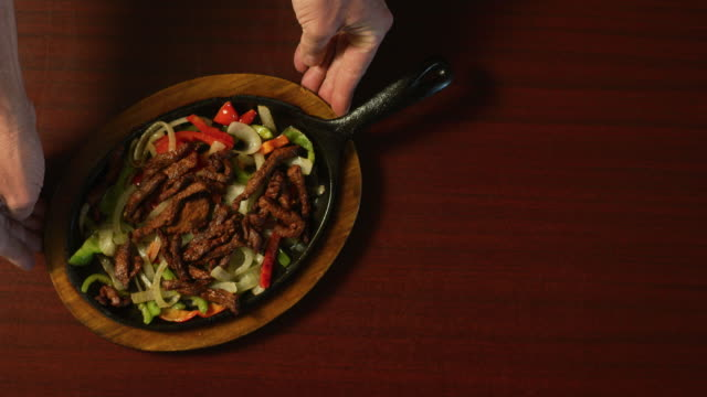 Directly Overhead Shot of a Person Placing a Plate of Steaming Beef Fajitas and Vegetables on a Table