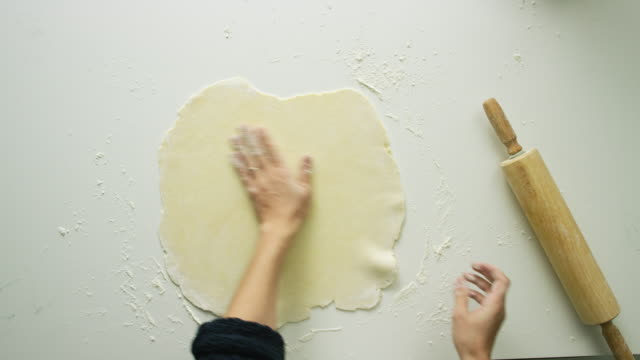 Directly Overhead Shot of a Woman's Hands Rolling out a Large Sheet of Pastry Dough with a Wooden Rolling Pin and Turning It Over as She Works