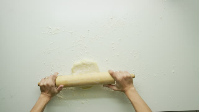 directly overhead shot of a woman's hands rolling out a large sheet of pastry dough with a wooden rolling pin and turning it over on a white table - impasto video stock e b–roll