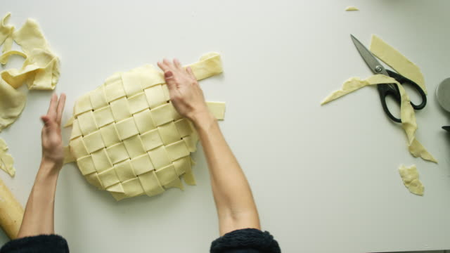 Directly Overhead Shot of a Woman's Hands Weaving Strips of Pastry Dough Together to Form a Lattice Pie Top Crust Then Trimming the Edges with Scissors