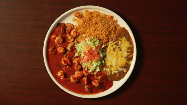 Directly Overhead Shot of Hands Pulling Away from a Table with a Plate of Shrimp, Mushrooms, Red Sauce, and Mexican Beans and Rice Directly Overhead Shot of Hands Pulling Away from a Table with a Plate of Shrimp, Mushrooms, Red Sauce, and Mexican Beans and Rice positioning stock videos & royalty-free footage