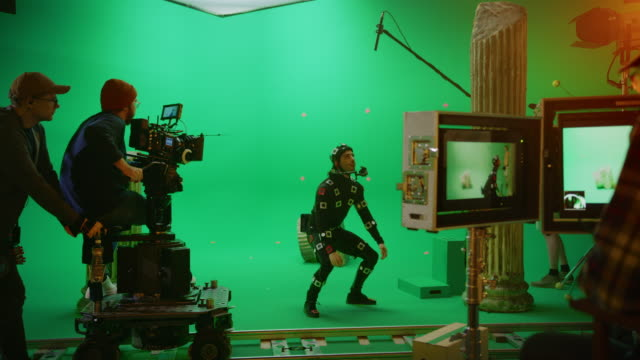 Director Commands Camera Operator to Start shooting Green Screen CGI Scene with Actor Wearing Motion Tracking Suit and Head Rig. Big Film Studio Professional Crew Shooting Blockbuster Movie Director Commands Camera Operator to Start shooting Green Screen CGI Scene with Actor Wearing Motion Tracking Suit and Head Rig. Big Film Studio Professional Crew Shooting Blockbuster Movie group of objects stock videos & royalty-free footage