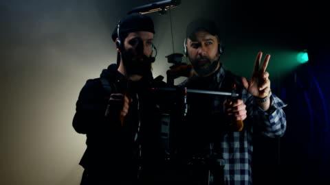 regista che istruisce un cameraman su un set cinematografico - filmare video stock e b–roll