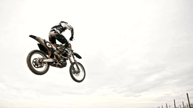 SLO MO Dirt biker jumping over dirt ramp video
