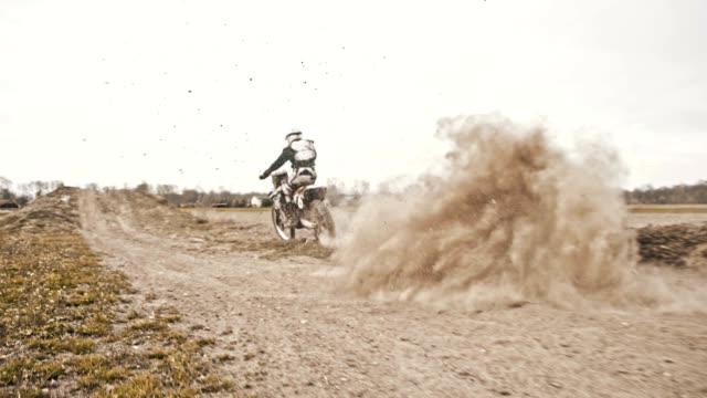 slo mo dirt biker speeding through the turn - motocross video stock e b–roll