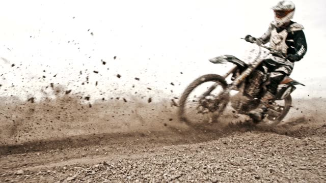 vídeos de stock e filmes b-roll de slo mo dirt bikers riding fast through the turn - estrada em terra batida