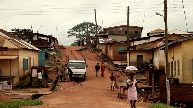 vídeos de stock e filmes b-roll de uma estrada em terra batida na região central do gana - aldeia