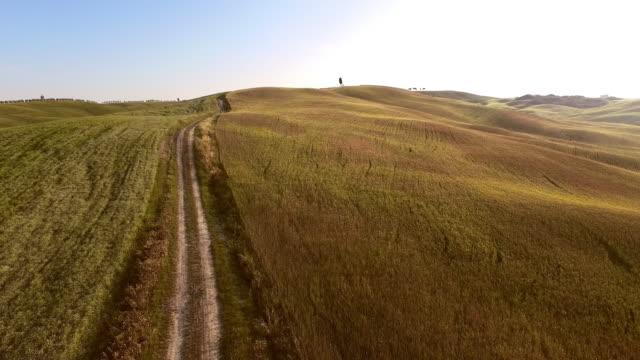 vídeos de stock e filmes b-roll de aérea de sujidade estrada rural tuscan - multicóptero