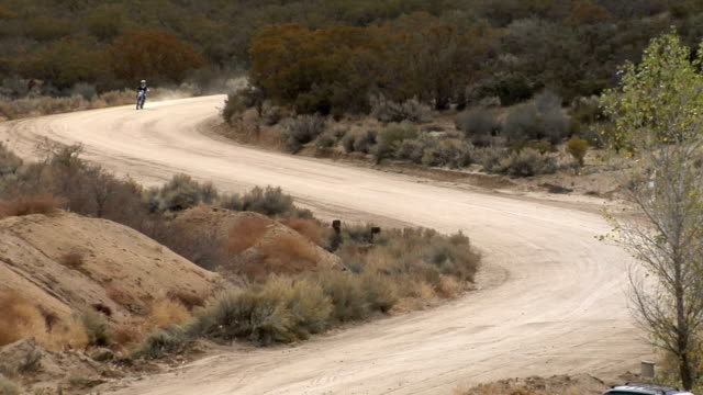 solitario dirtbike su una strada del deserto - freestyle motocross video stock e b–roll