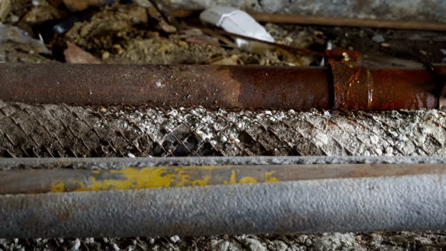 dirty basement of old house leaking rusty pipes water on pipe repair clamps - rusty stock videos & royalty-free footage
