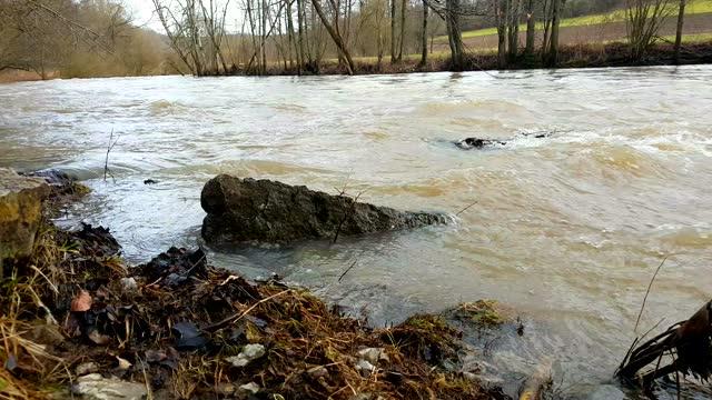 vidéos et rushes de eau brune sale coulant le long d'une rivière pendant une inondation - marron couleur