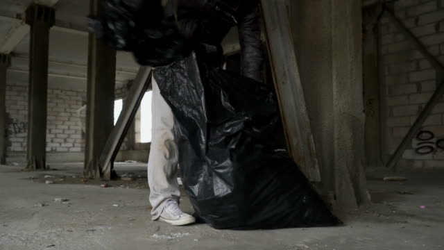 Dirty bum searches something in garbage bag video