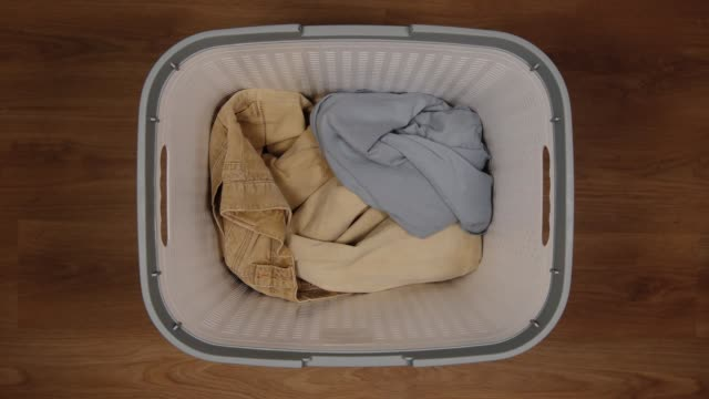 top view: dirty clothes are filling a laundry basket on a floor - stop motion - cestino video stock e b–roll