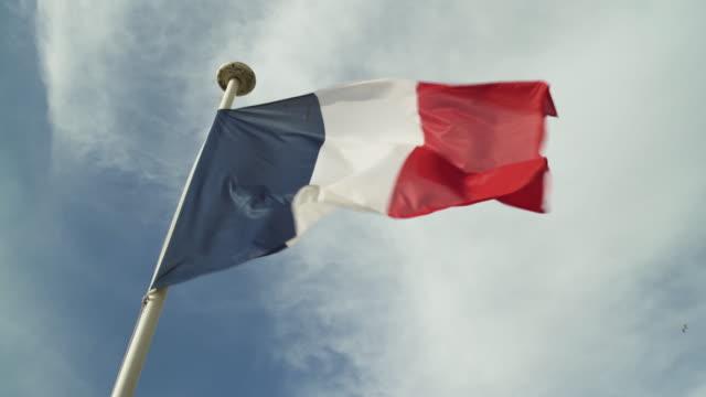 vídeos de stock, filmes e b-roll de bandeira francesa suja no vento no céu azul nebuloso na praia de deauville, france. pássaros que passam sobre durante o dia. baixo ângulo 4k uhd. tempo ventoso. - frança