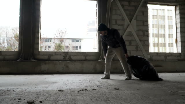 Dirty homeless drags a garbage bag in abandoned building video