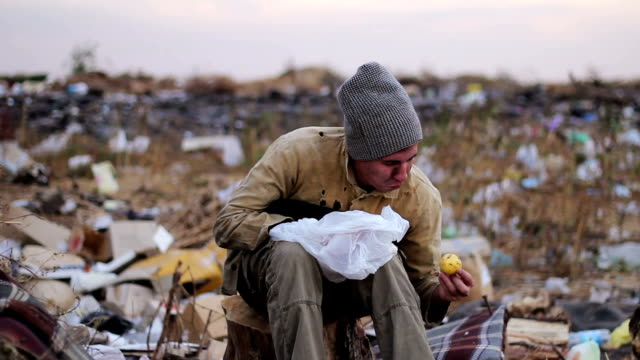 dirty homeless man sits on a stump in the trash and eat the food from the bag dirty homeless man sits on a stump in the trash and eat the food from the  bag homeless person stock videos & royalty-free footage